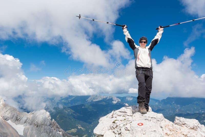 Der weibliche Bergsteiger, der ein erfolgreiches feiert, steigen auf stockfotografie