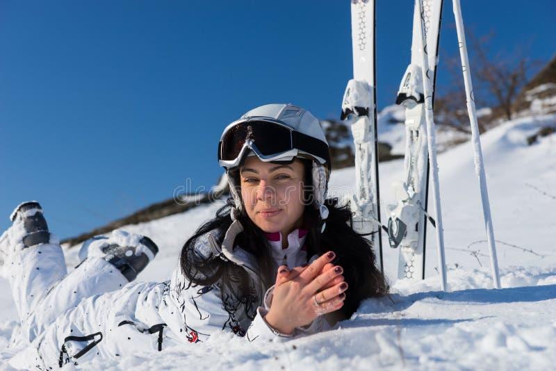 Der weibliche Skifahrer, der auf Schnee liegt, bedeckte Bergabhang lizenzfreie stockfotografie