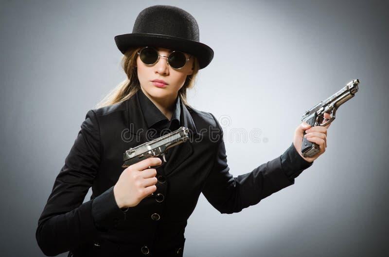 Der weibliche Spion mit Waffe gegen Grau lizenzfreie stockfotos