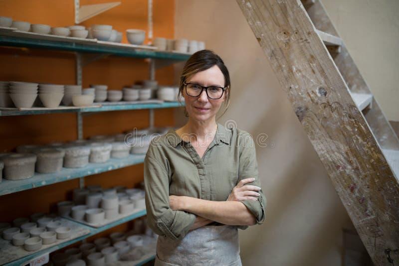 Der weibliche Töpfer, der mit den Armen steht, kreuzte in der Tonwarenwerkstatt lizenzfreie stockfotos