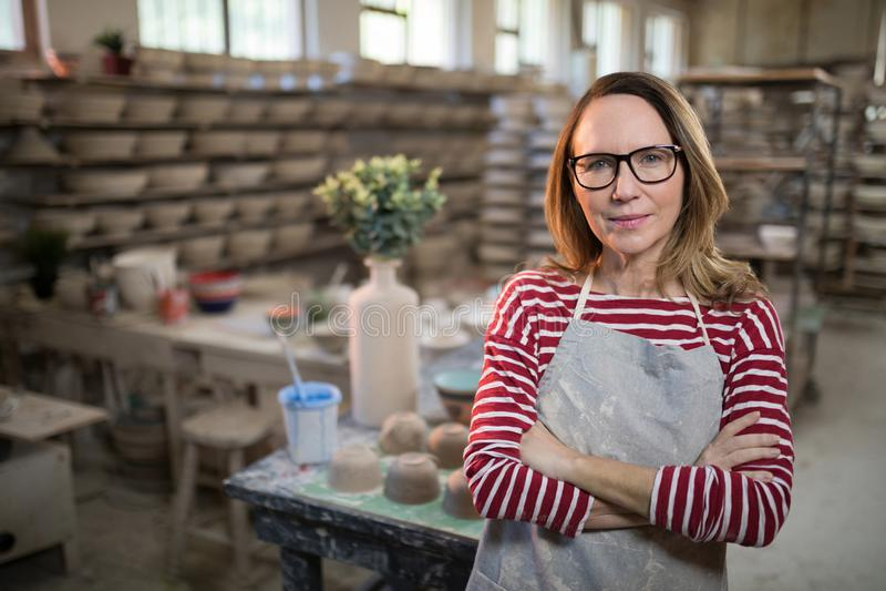 Der weibliche Töpfer, der mit den Armen steht, kreuzte in der Tonwarenwerkstatt stockfotografie
