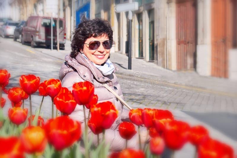 Der weibliche Tourist, der Kamera gegen Tulpe lächelt und betrachtet, blüht in Porto, Portugal stockfotografie