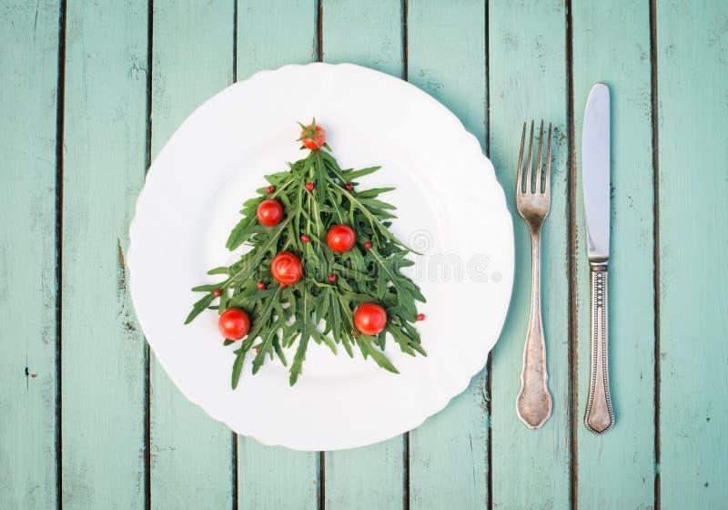 Der Weihnachtsbaum, der von den Arugula- und Kirschtomaten auf Weiß gemacht wird, flechten stockfotografie