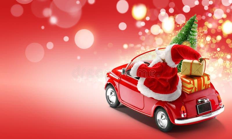 Der Weihnachtsmann fährt rotes Auto mit Geschenkkartons und Weihnachtsbaum auf rotem Hintergrund mit Tellern stockbild