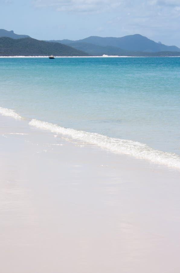 Der Whitehaven-Strand in den Pfingstsonntagen in Australien mit einem kleinen Boot im Abstand stockfotos