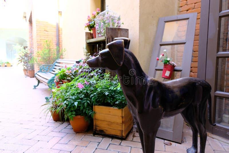 Der Windhundhund, der durch Metallcastings gemacht wird, ist- von der Dekoration und vom Blumentopf groß stockfotos
