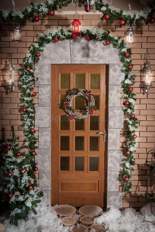 Der Winterkranz, der an einer Tür von Weihnachten hängt, verzierte Haus stockfoto