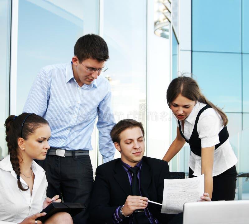 Der Wirtschaftler mit vier Jungen arbeiten zusammen lizenzfreies stockfoto