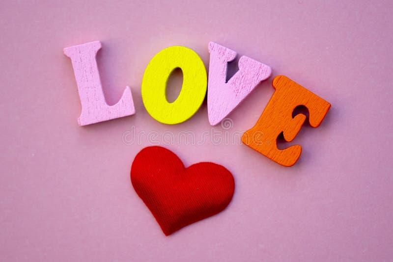 Der Wortliebe Valentinstag mit bunten hölzernen Buchstaben Liebe und Herz - ein Symbol des Valentinstags Makro lizenzfreie stockfotografie