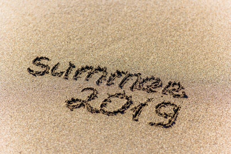 Der Wortsommer geschrieben in den Sand auf einen Strand lizenzfreie stockfotos