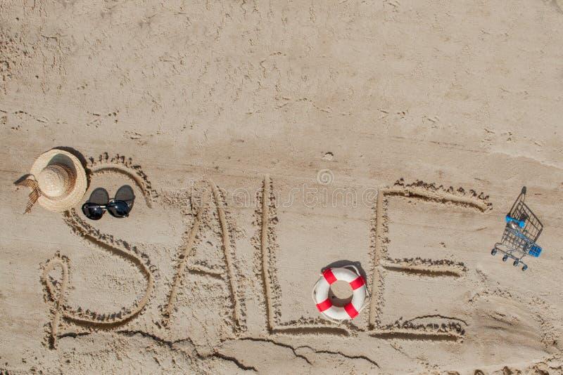 Der Wortverkauf wird auf dem Sand gemalt Kamm-MuschelSeashell auf Rosa Ansicht von oben Das Konzept des Sommers, Sommer kanikkuly stockbild