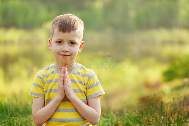 Der Yoga-Haltung des kleinen netten Jungen des Porträts übender Tag im Frühjahr stockfoto