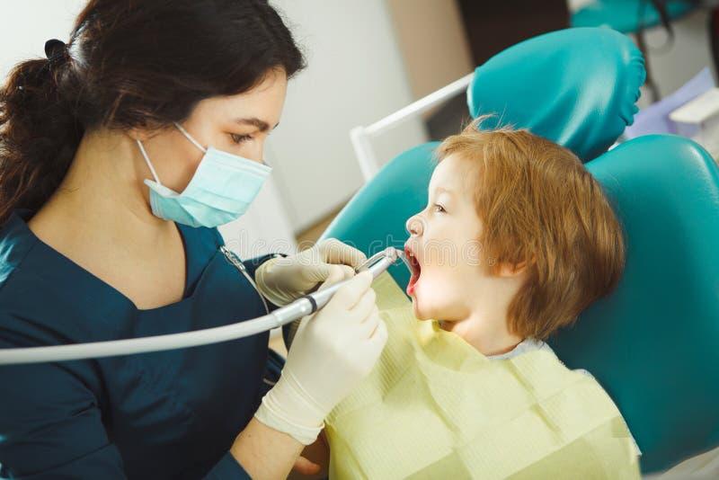 Der Zahnarzt, der Bohrgerätzahn zum Kind, kleiner Patient öffnete vorbereitet ergeben, seinen Mund und saß auf Stuhl stockfotografie