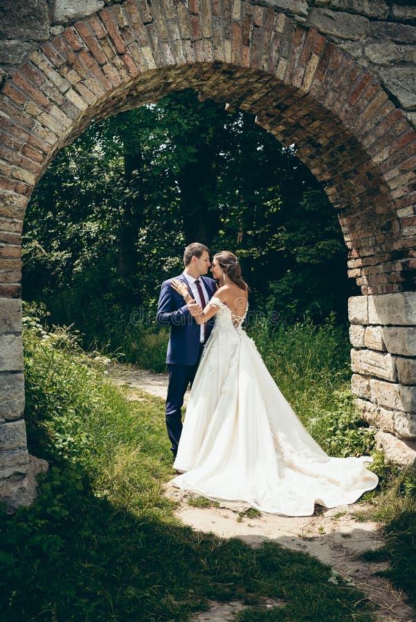 Der Zauber, der Jungvermähltenpaare unter dem Steinbogen in der Waldbraut umarmt, hat das Kleid mit bloßer Rückseite lizenzfreies stockbild