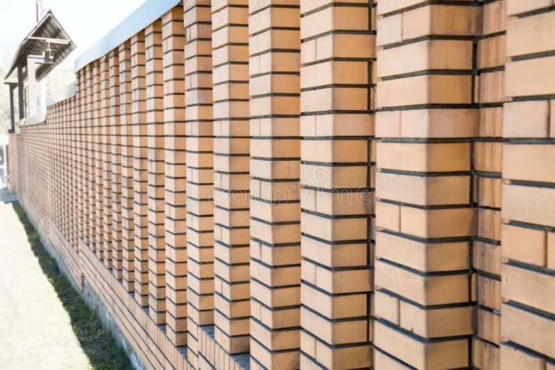 Der Zaun wird vom Sand-farbigen Ziegelstein mit einer Perspektive hergestellt stockbild
