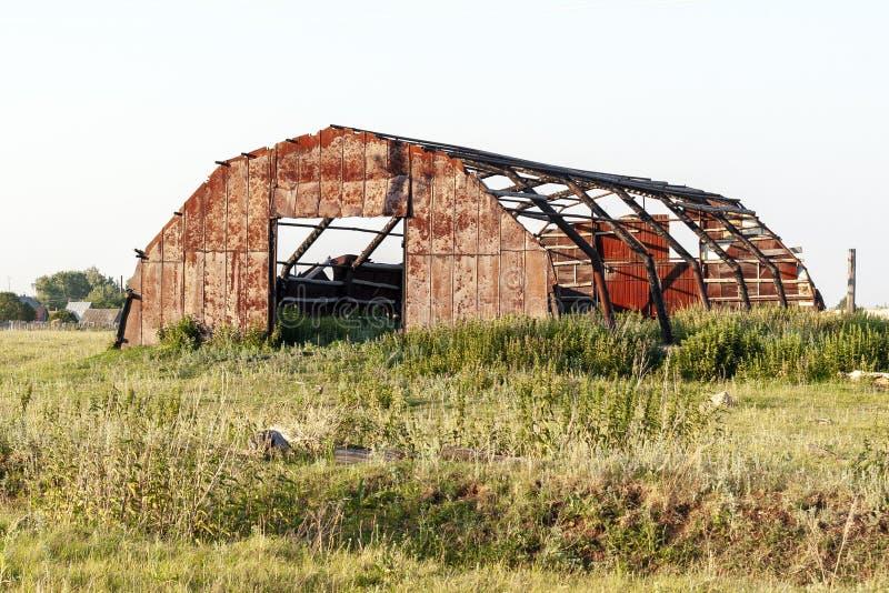 Der zerstörte Metallhangar in der Landschaft stockbild