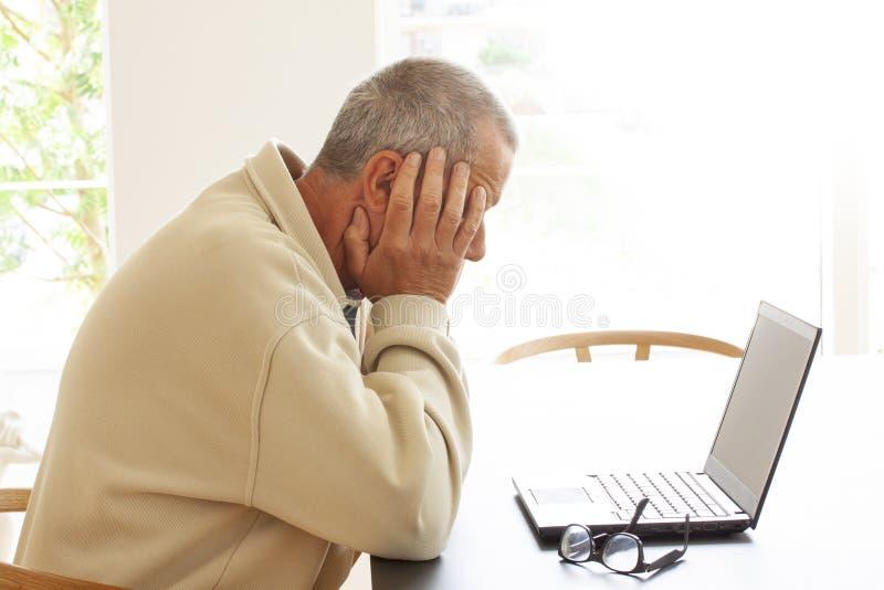 Der zufällige gekleidete Mann, der durch eine Laptop-Computer sitzt, versteckt seinen Kopf in der Verzweiflung Ein Paar Gläser, d stockfotografie