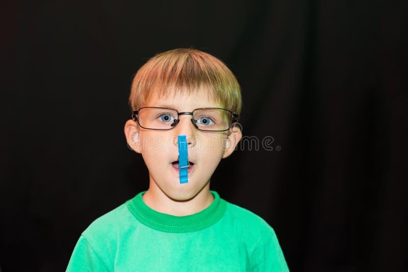 Der zufällige Junge in den Gläsern setzte an eine Wäscheklammer auf seine Lippe und Blicke an der Kamera, gegen einen dunklen Hin lizenzfreie stockbilder