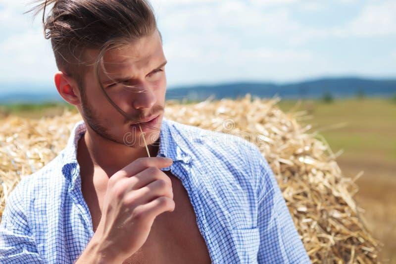Der zufällige Mann, der mit Stroh im Mund im Freien ist, schaut weg stockfoto