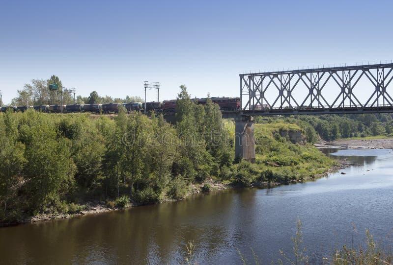 Der Zug fährt auf die Brücke durch den Fluss Narva Estland lizenzfreies stockbild