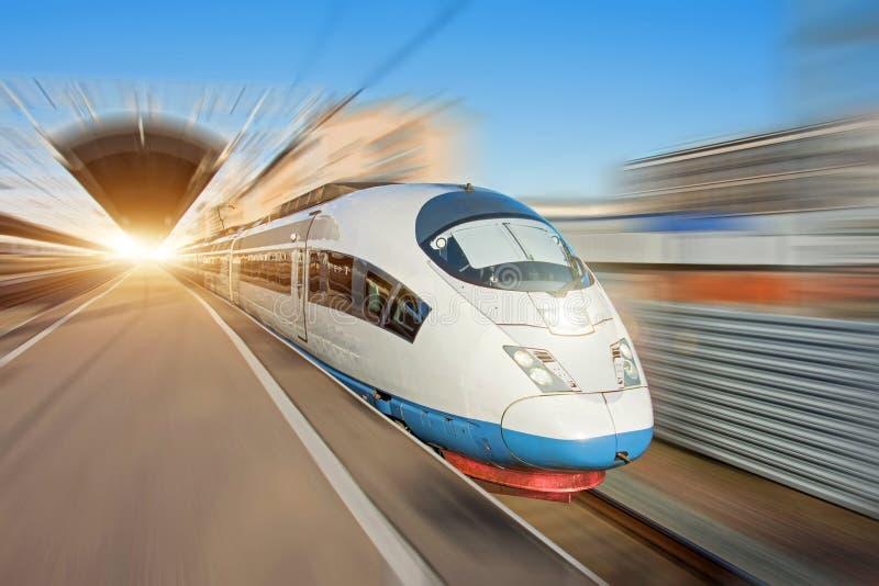 Der Zug reist von der Plattform der Haltestelle ab und reist an der hohen Geschwindigkeit durch die Stadt lizenzfreies stockbild