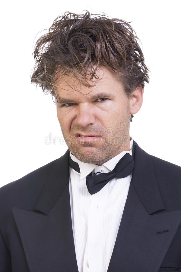Deranged angry man in a tuxedo. Portrait of mad deranged Caucasian man with long messy hair wearing messed up black tuxedo on white background stock image