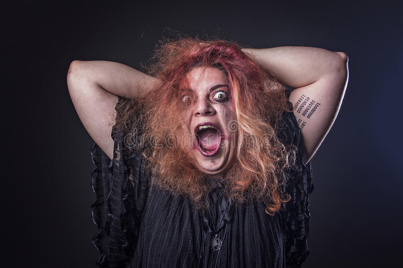 Deranged woman screaming. Mad girl with a dangerous face screaming loudly stock photo