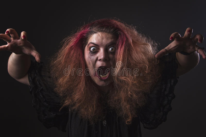 Deranged woman screaming. Mad girl with a dangerous face screaming loudly stock photos