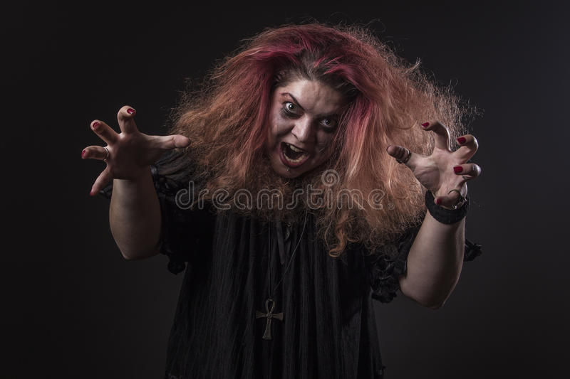 Deranged woman screaming. Mad girl with a dangerous face screaming loudly stock images