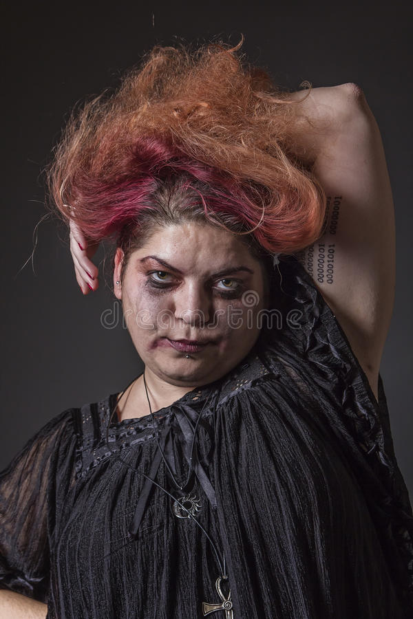 Deranged woman in a terrible state. Mad horror girl giving a killer look to the camera royalty free stock photo
