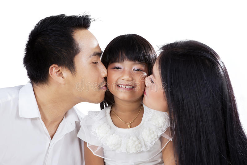 deras kyssande föräldrar för dotter royaltyfri bild