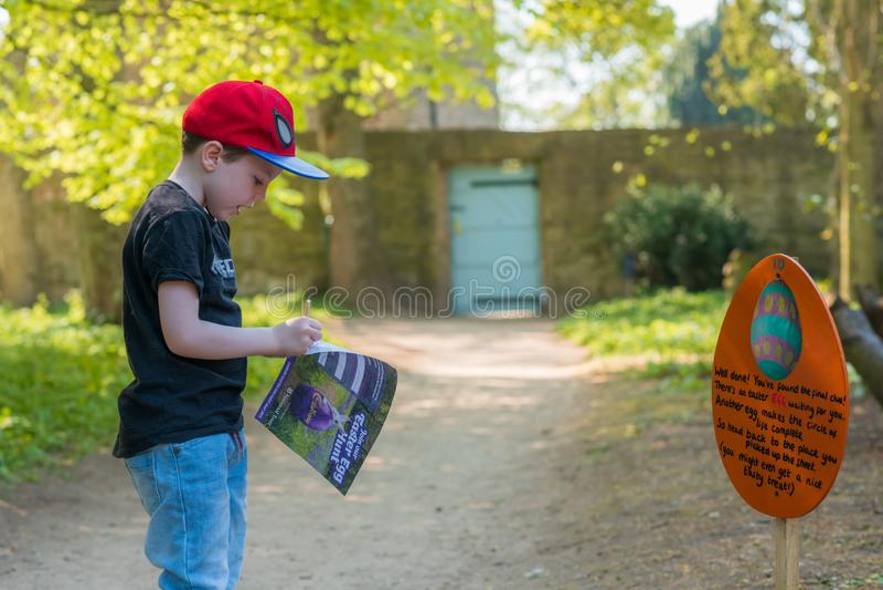 DERBYSHIRE, REINO UNIDO - 21 DE ABRIL DE 2019: Un pequeño niño participa en una caza del huevo de Pascua en Hardwick Pasillo imagen de archivo
