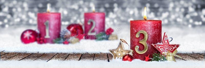 derde zondag van komst rode kaars met gouden metaalaantal op houten planken in sneeuwvoorzijde van zilveren bokehachtergrond stock foto