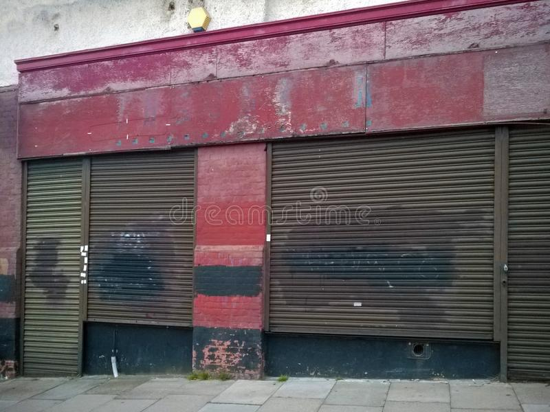 Derelict abandoned store with shuttered vandalized shop front with peeling red paint on an urban street royalty free stock images