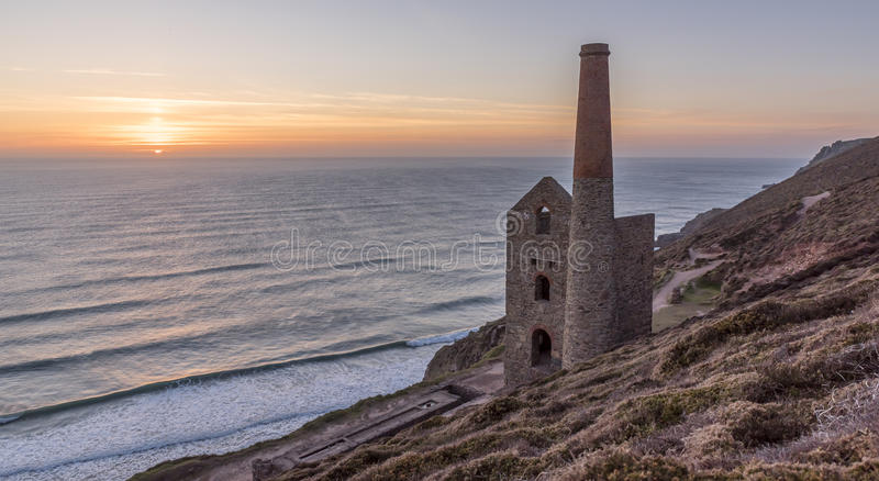 Derelict Cornish tin mine, on the cliff edge, against a blue sky stock photo