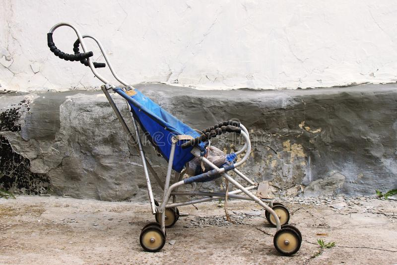 Derelict and dis guarded old and dirty vintage pram of pushchair dumped in an old background. Summer stroller as a symbol of a byg stock photo