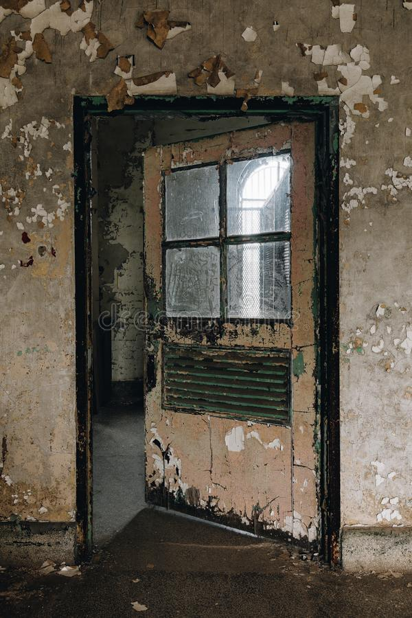 Derelict Door - Ohio State Reformatory Prison - Mansfield, Ohio. A view of a derelict door with four panes of glass at the library inside the closed Ohio State royalty free stock photos