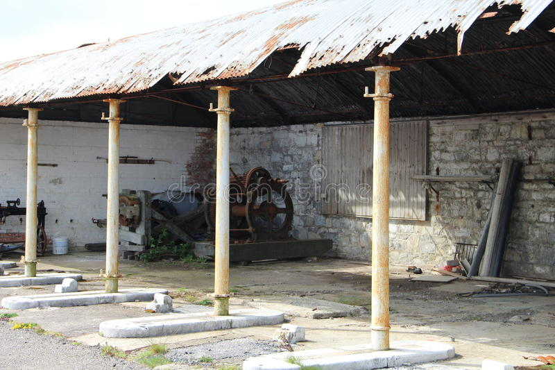 Derelict barn with some old tools. Derelict and empty barn with some old tools in Ireland. The roof is supported by metal poles stock photos
