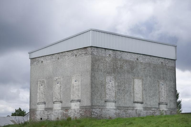 Derelict grey haunted building on hill which is an old power plant house stock image