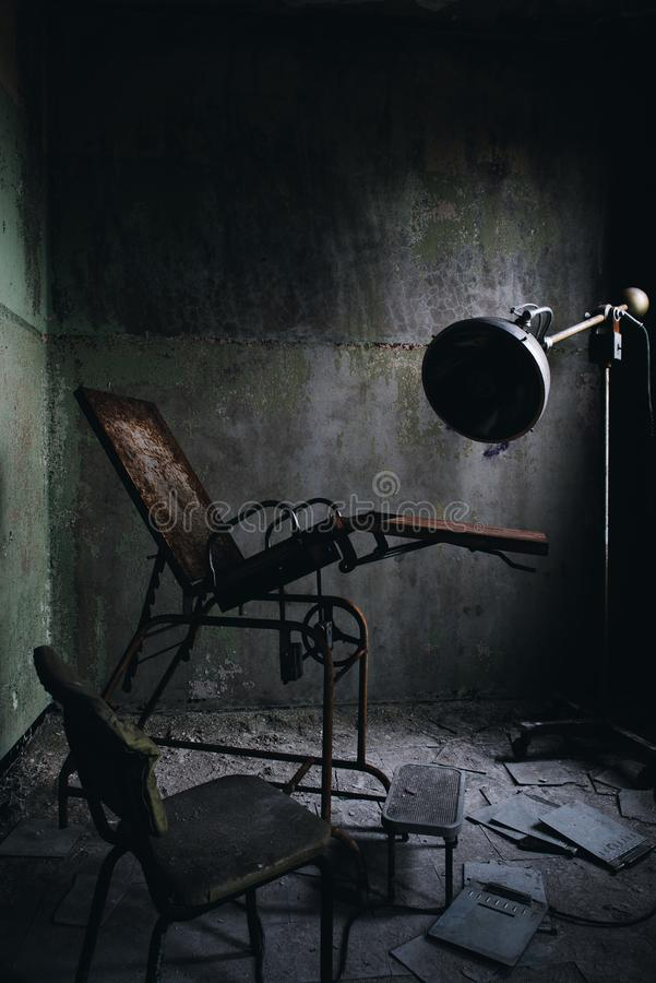 Derelict Gynecological Examination Chair - Abandoned Westboro State Hospital - Massachusetts. A view of a derelict gynecological examination chair inside the stock image