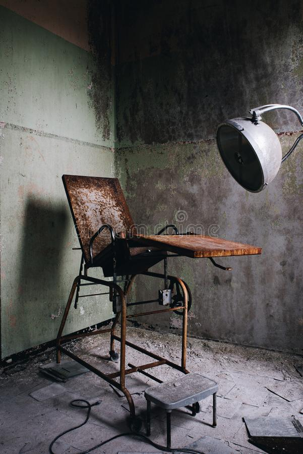 Derelict Gynecological Examination Chair - Abandoned Westboro State Hospital - Massachusetts. A view of a derelict gynecological examination chair inside the royalty free stock images