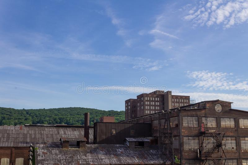 Derelict industrial warehouse with modern commercial building and forested hillside beyond stock photos
