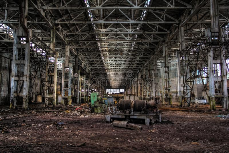 Derelict large dark industrial machinery hall of abandoned factory royalty free stock photography
