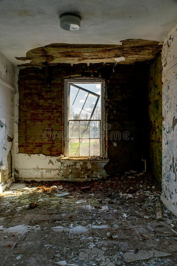 Derelict Room & Broken Window - Abandoned Knox County Infirmary - Ohio. A view of a derelict room with a broken window at the abandoned Knox County Infirmary royalty free stock photos