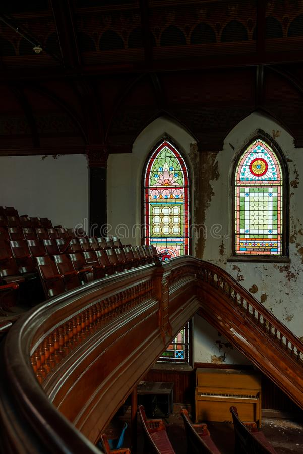 Derelict Sanctuary with Stained Glass Windows & Staircase - Abandoned Church - Lowell, Massachusetts. A wide view of a derelict sanctuary with stained glass royalty free stock photos