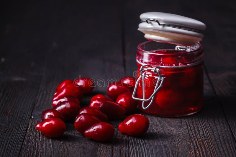 Dereniowy jagodowy dżem i dojrzałe cornel jagody na wiejskim drewnianym tle zdjęcie stock