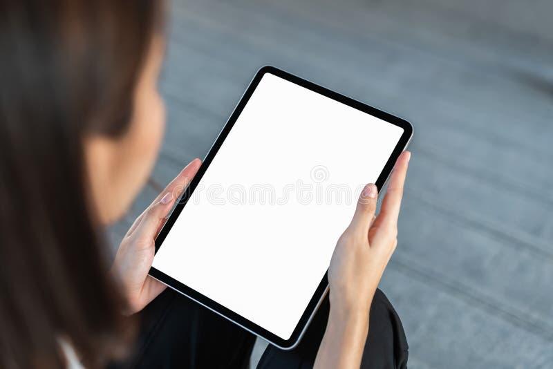Derida su della mano femminile che tiene lo schermo in bianco della compressa digitale sull'isolato su Prenda il vostro schermo p fotografia stock