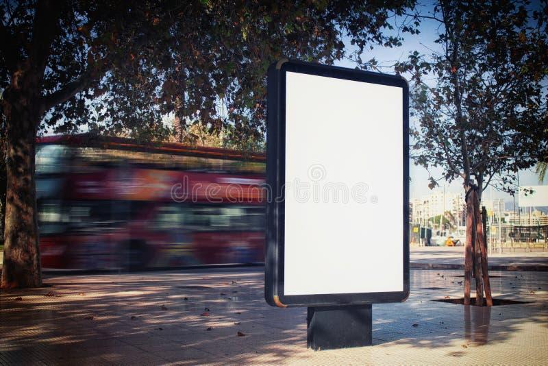Derida su della scatola leggera verticale bianca dello spazio in bianco su una via, in una città contro lo sfondo di un bus turis fotografia stock