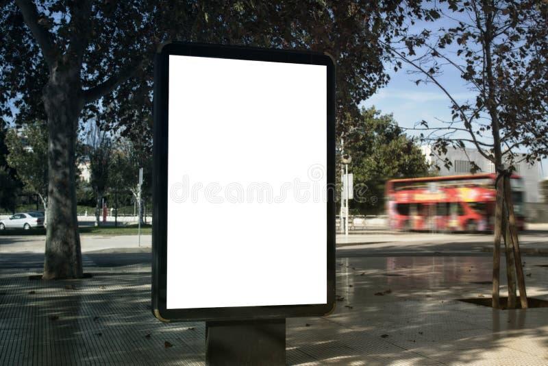 Derida su della scatola leggera verticale bianca dello spazio in bianco su una via, in una città contro lo sfondo di un bus turis fotografie stock