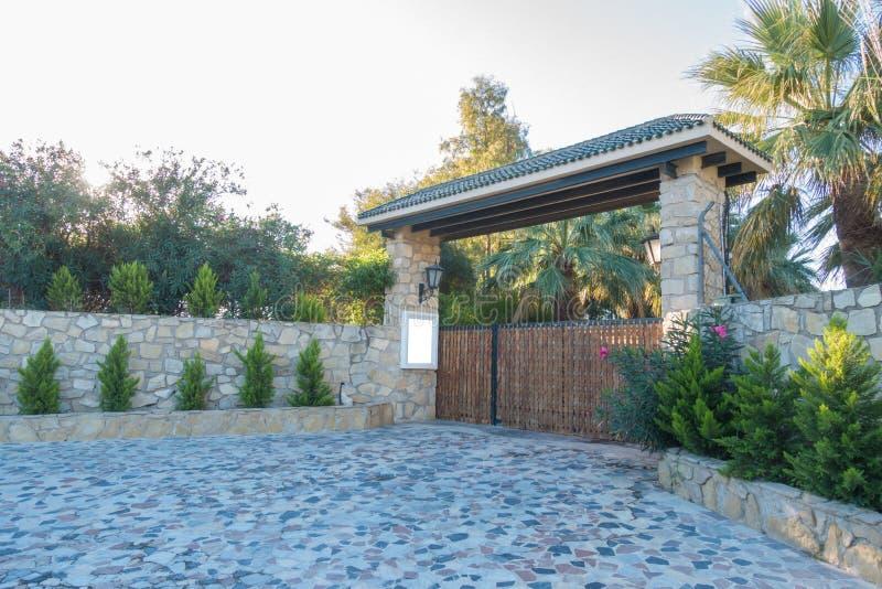 Derida su vicino al portone all'iarda privata della casa Portoni di legno e un alto recinto di pietra fotografia stock
